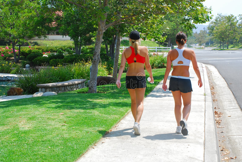 Two Women Walking. Two young women in exercise clothing on an walk down a pretty street stock images