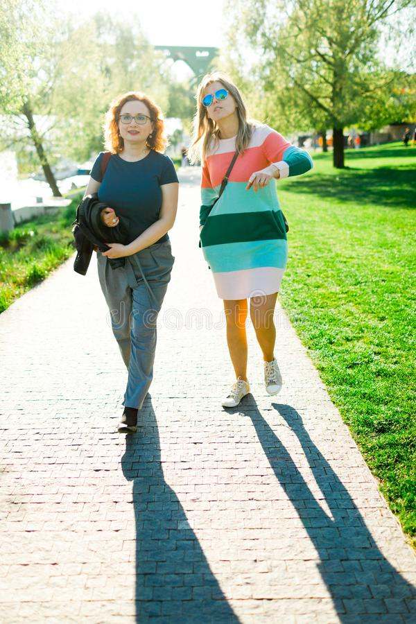 Two women walking along the waterfront - shadows stock photography