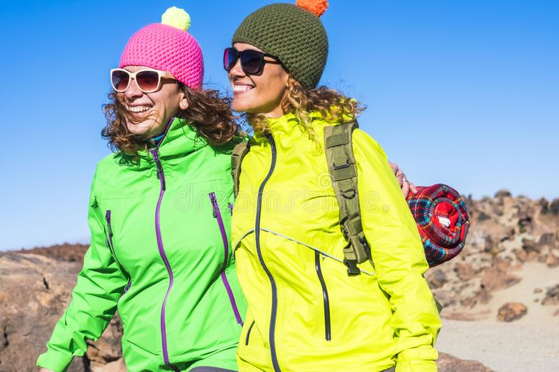 Two women walking and hiking together at the mountain - friendship goal smiling - happy couple of girls with cold and winter royalty free stock photography