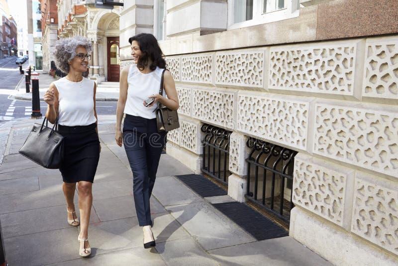 Two women walking in the street talking, full length royalty free stock image