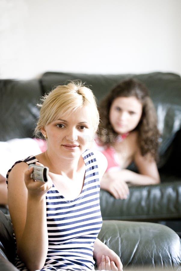 Two women watching tv stock photos