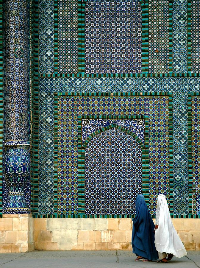 Two women wearing burqas walk past the Blue Mosque in Mazar i Sharif, Afghanistan. The Blue Mosque in Mazar-i-Sharif, Balkh Province in Afghanistan. Two women royalty free stock photography
