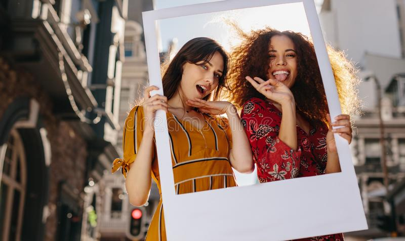 Female friends posing with a blank picture frame royalty free stock photos