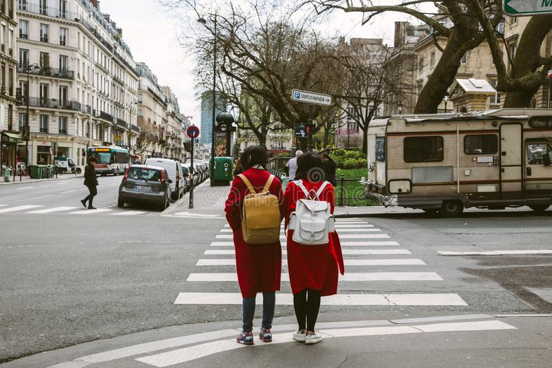 Two Women Wearing Red Coats With Backpacks royalty free stock image