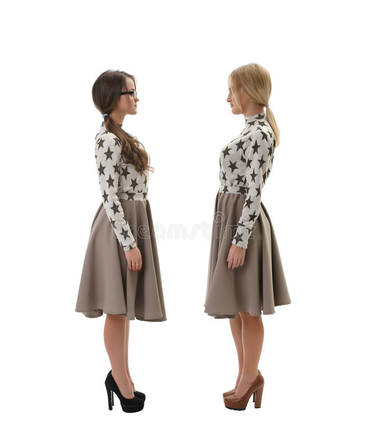 Two women wearing same clothes isolated on white. Side view full length shot of young women wearing high heels and same dresses standing on white isolated studio royalty free stock image