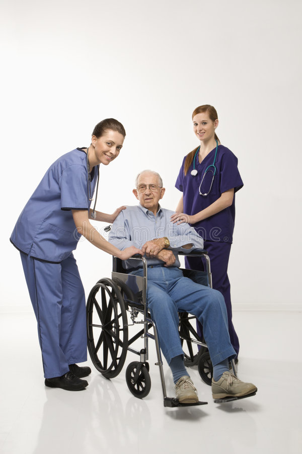 Two women wearing scrubs with elderly man in wheelchair. royalty free stock image