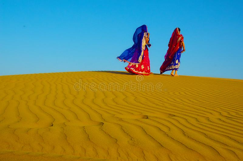 Two women wearing traditional ethnic indian outfits walking on a yellow sand dune stock photos