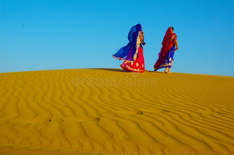 Two women wearing traditional ethnic indian outfits walking on a yellow sand dune. In the hot summer desert against blue sky, Jaisalmer, Rajasthan, India royalty free stock photos