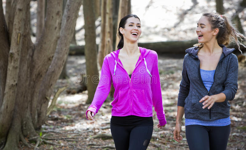 Two women wlaking in the middle of the woods royalty free stock image