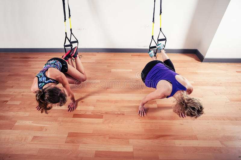 Two women working out with straps in gym royalty free stock photos