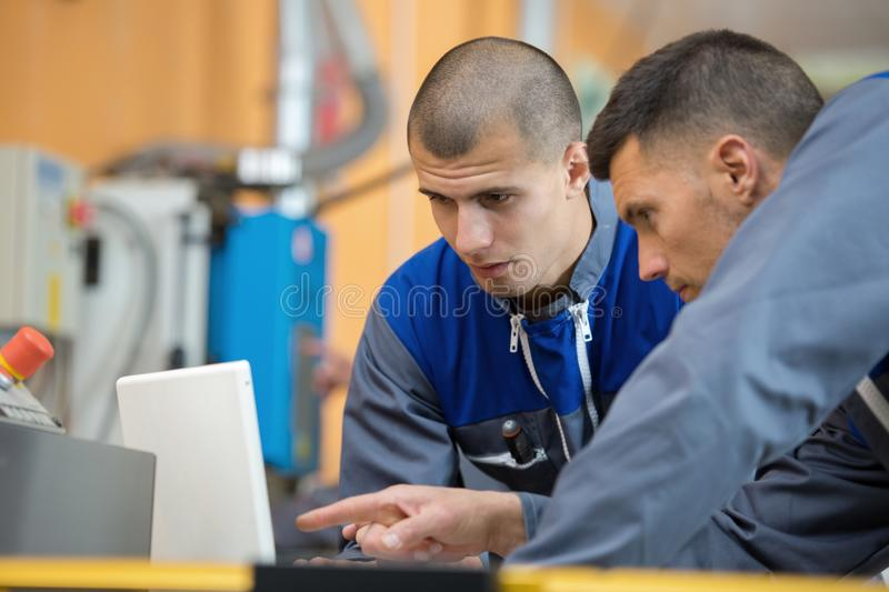 Two wood designer working with laptop in workshop royalty free stock photo