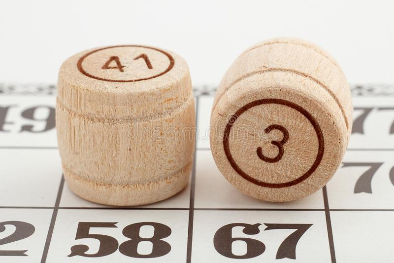 Two wooden barrel numbers and card for a lotto game on a white background. Close-up view stock photography