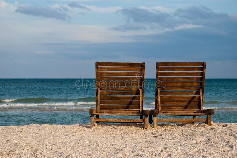 Two wooden brown chaise longue on the beach sand sea shore blue sky wave summer stock photography