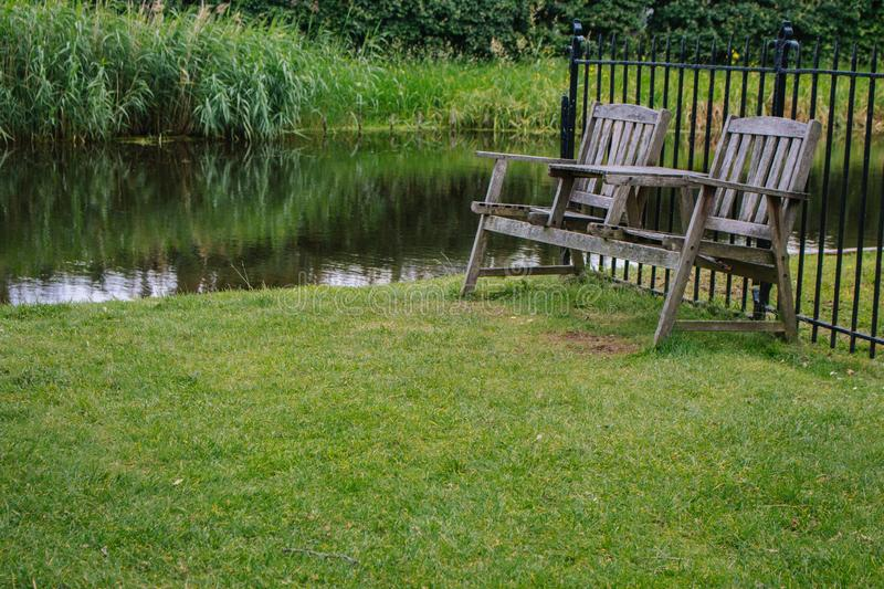Two wooden chairs in the backyard near pond. Old outdoor furniture in summer garden. Empty quiet place for relax. stock photos
