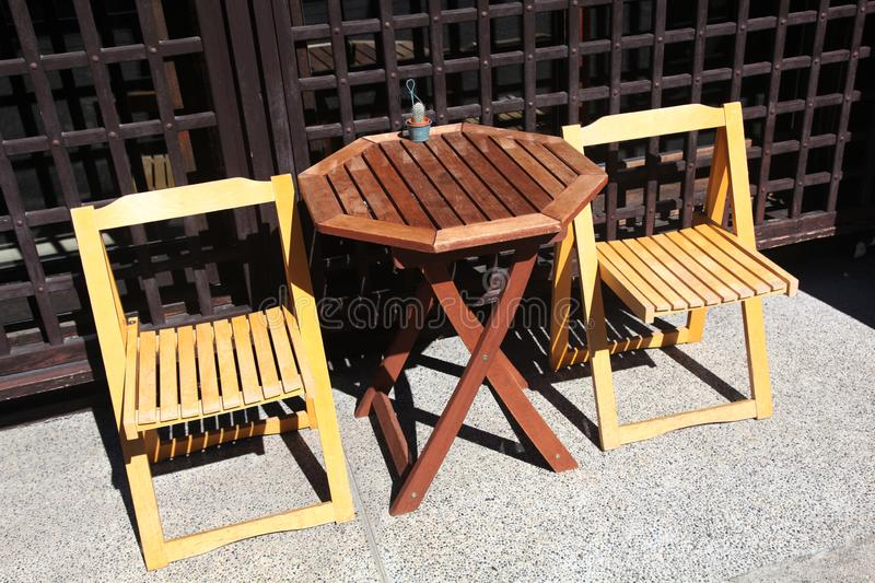 Two wooden chairs with a wooden table mismatched stock images