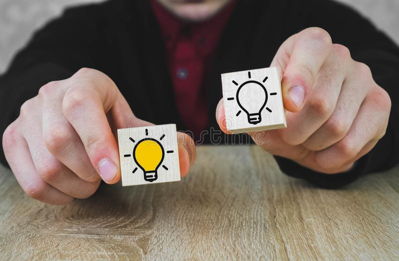 Two wooden cubes in the hands of a person in a suit, one of which is lit in yellow, which symbolizes the new idea, the concept of stock photography