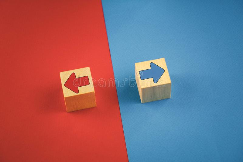 Two wooden cubes with red and blue arrows on a red and blue background look in different directions. Business, icon, achievement, blog, bulb, competitor royalty free stock photography