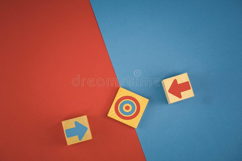 two wooden cubes with red and blue arrows directed towards the target, which means striving for the goal, competition stock images