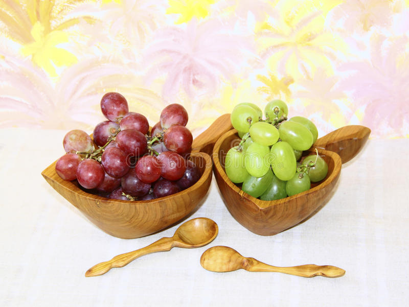 Two wooden cup with green and pink grapes stock photo
