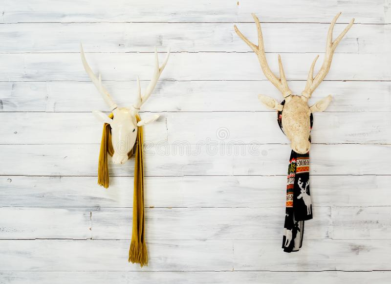 Two wooden deer heads with warm scarfs on wall. Scandinavian style decor. Text space royalty free stock image