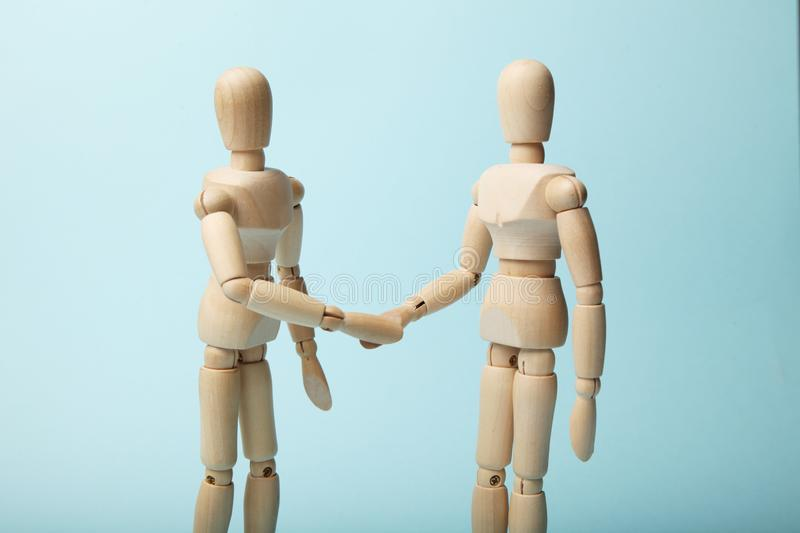 Two wooden figures of man shake hands.  stock images