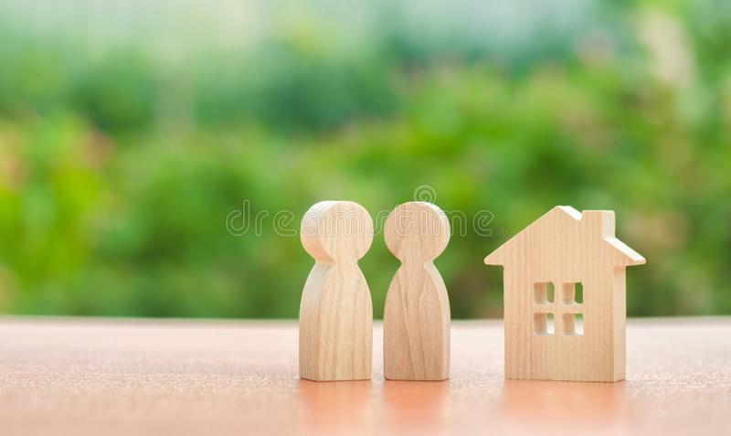 Two wooden figures of people and a house on a nature background. concept of affordable housing, mortgages. For buying a home for young families and couples stock photos