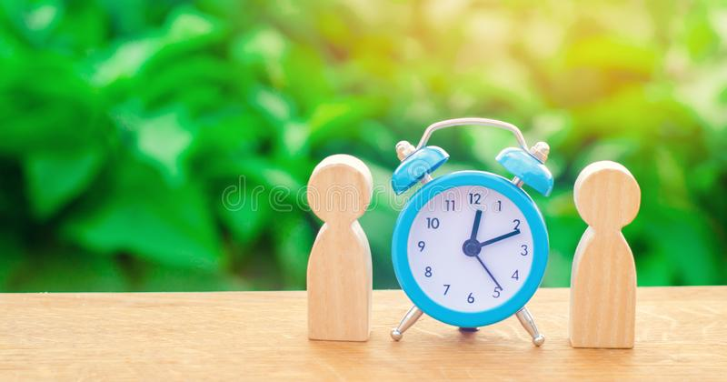 Two wooden figures of people standing near a blue alarm clock on a green background. The concept of time and planning. Discussion stock images