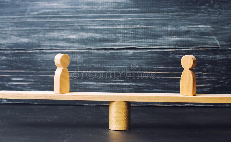 Two wooden figures stand on the scales of justice. Business concept of mutual benefit and success of business partners. successful. Transaction stock images