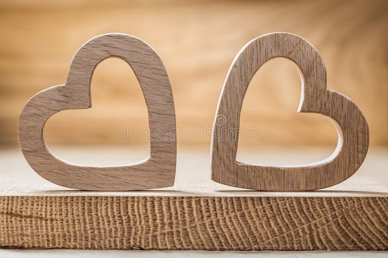 Two wooden  hearts on wood background close up view stock photo