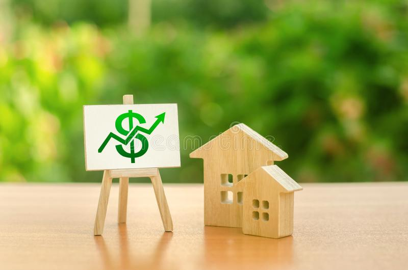 Two wooden houses and a green up arrow on the sign. Real estate value increase. Rising prices for housing, building maintenance. Supply and demand. High rates stock photos