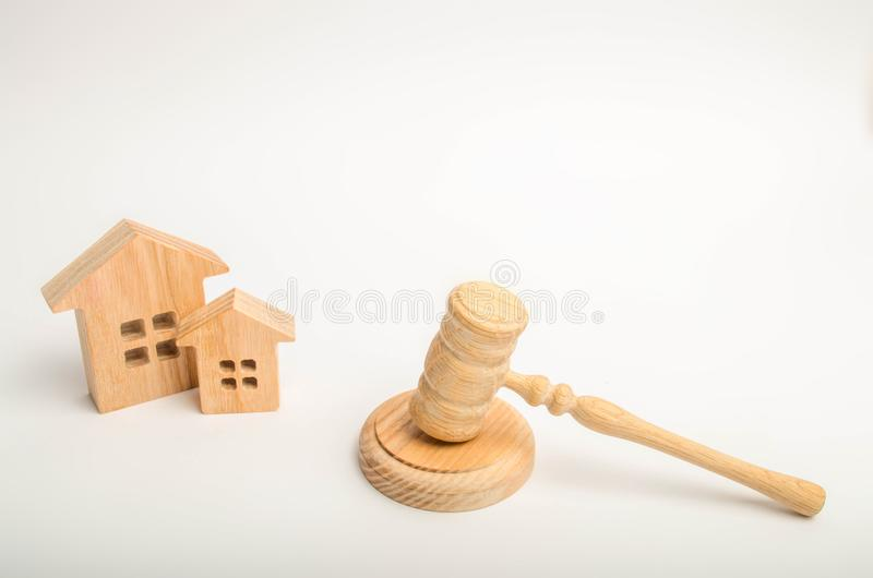 Two wooden houses and a hammer of the judge on a white background. court cases on property and real estate. Confiscation and natio. Nalization, real estate scam stock photo