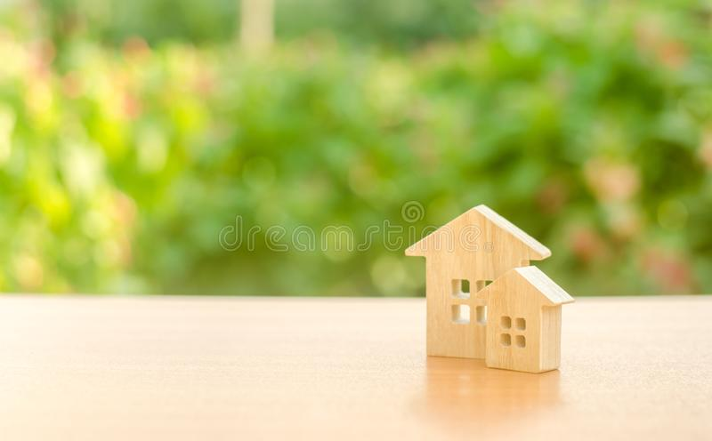 Two wooden houses on a nature background. Buying and selling of real estate, construction. Apartments and apartments. City, settlement. Minimalism stock images