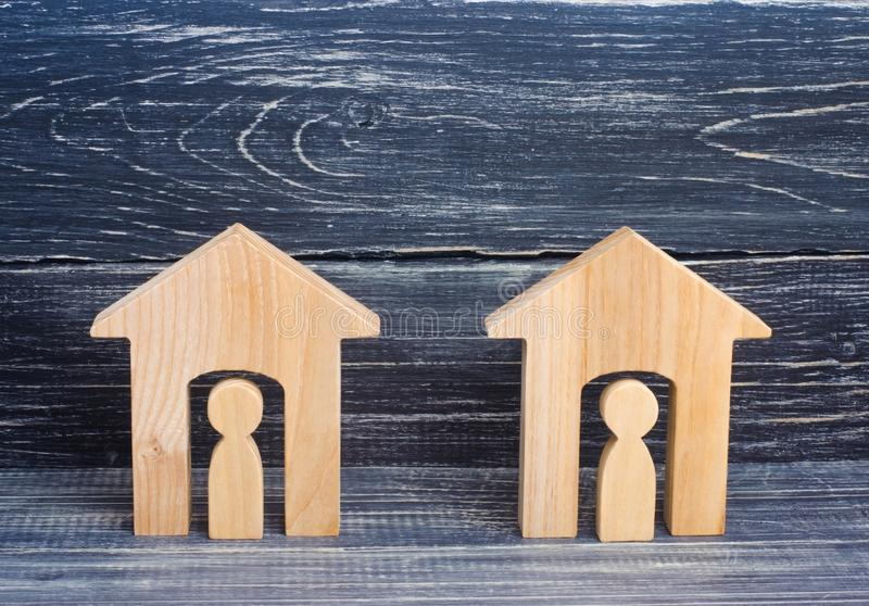 Two wooden houses with people on a black background. The concept of the district, its neighbors. Good-neighborly relations. Afford stock image