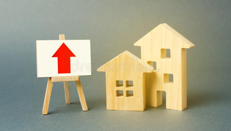 Two wooden houses and a red up arrow on the sign. Real estate value increase. Supply and demand. Rising prices for housing. Building maintenance. High rates of stock images