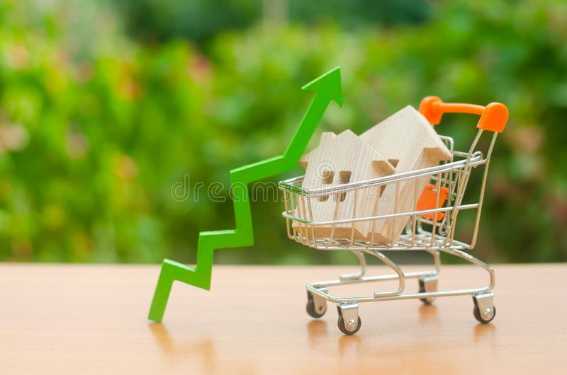Two wooden houses in a trading cart and green arrow up. Increasing cost and liquidity of real estate. Attractive investing. rising. Prices or renting. growth of royalty free stock photography