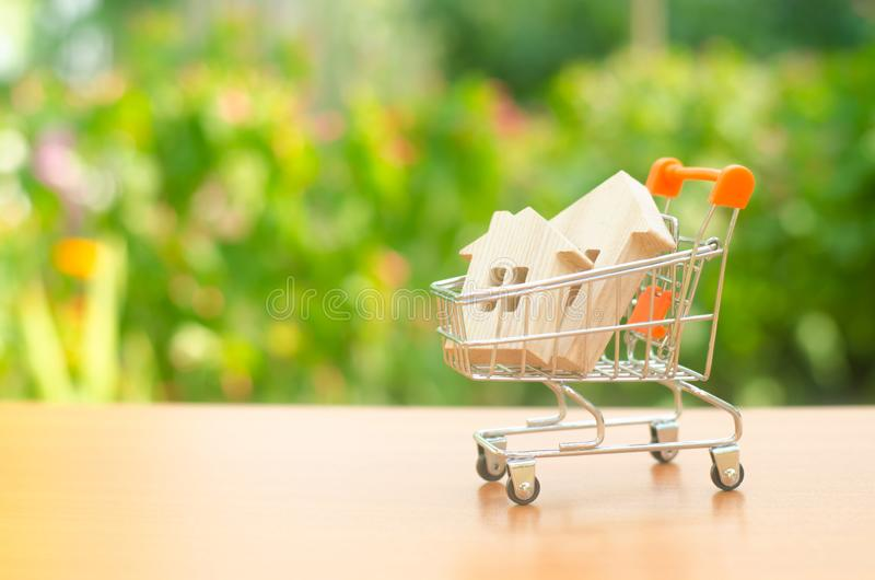 Two wooden houses in a trading cart on nature background. The concept of buying and selling real estate, renting. Attractive. Investing. rising prices. supply stock image