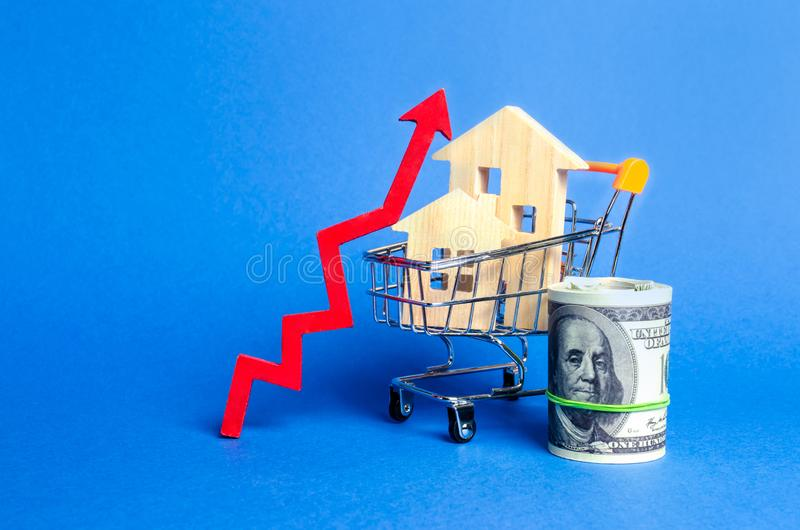 Two wooden houses in a trading cart and red arrow up and money bundle. Increasing cost and liquidity of real estate. Attractive. Investing. rising prices or stock photo