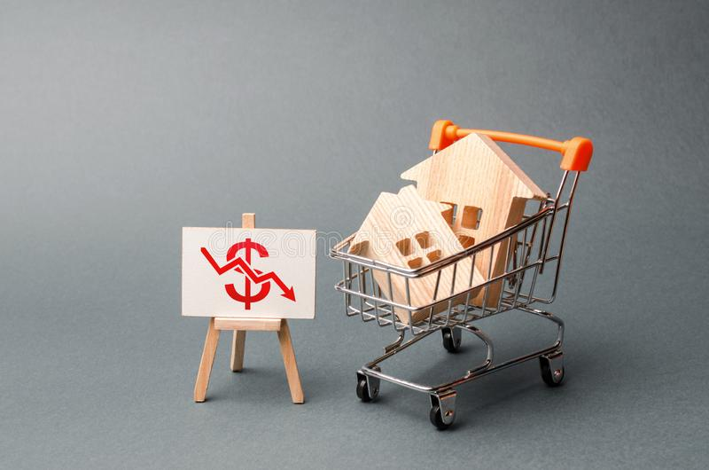 Two wooden houses in a trading cart and a stand with red arrow down. real estate value decrease. cheapening the rent or cost. Of buying a home. low liquidity stock image