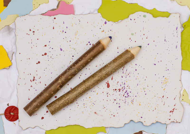 Two wooden pencil on torn paper stock photography