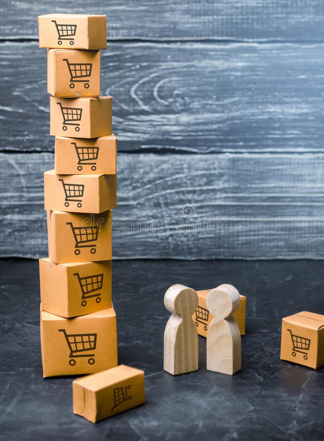 Two wooden people stand near a tower of boxes. buyer and seller, manufacturer and retailer. Discussion of the terms of the trading. Deal, the purchase of goods stock photography