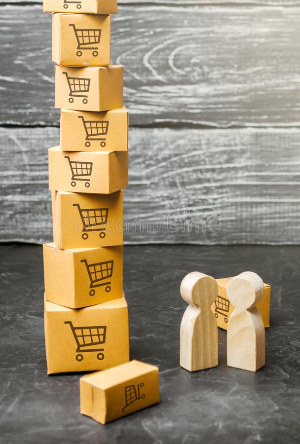 Two wooden people stand near a tower of boxes. buyer and seller, manufacturer and retailer. Discussion of the terms of the trading. Deal, the purchase of goods royalty free stock photos