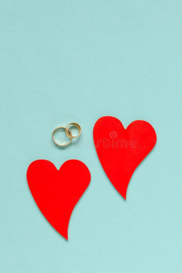 Two wooden red hearts and wedding rings on blue background royalty free stock image