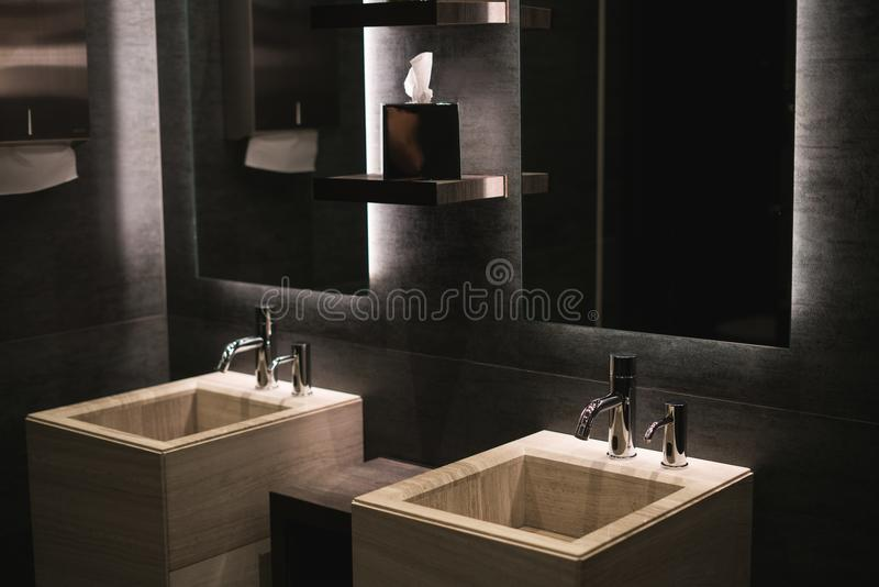 Two wooden sinks in a bathroom under two glass mirrors. Modern architecture and interior royalty free stock photos