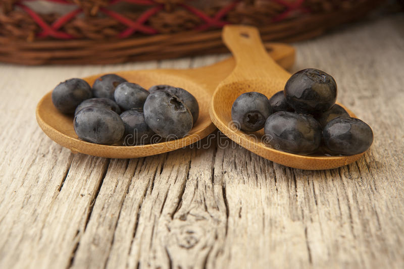 Two wooden spoons with fresh blueberries and wicker basket royalty free stock images