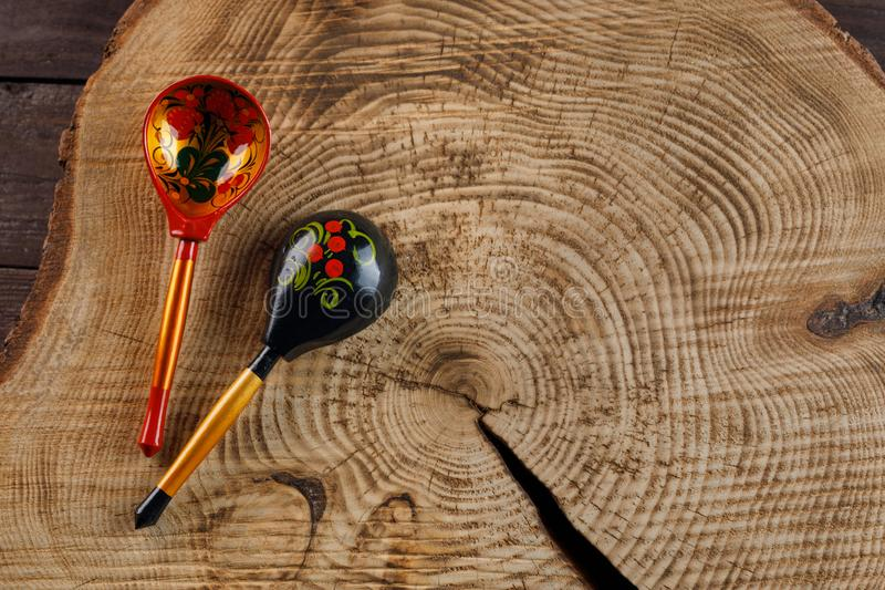 Two wooden spoons with a traditional Russian pattern on a wooden background. Khokhloma painting royalty free stock image