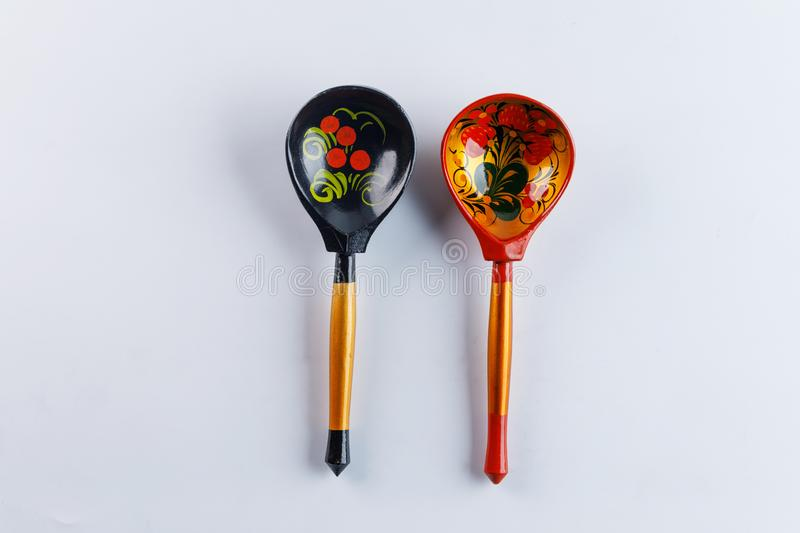 Two wooden spoons with a traditional Russian pattern on a white background. Khokhloma painting royalty free stock photos