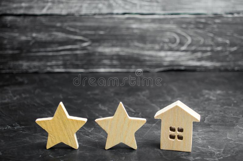 Two wooden stars and a house. Two star hotel or restaurant. Review of the critic. Quality of service and level of service. Rating. Of houses and private royalty free stock image