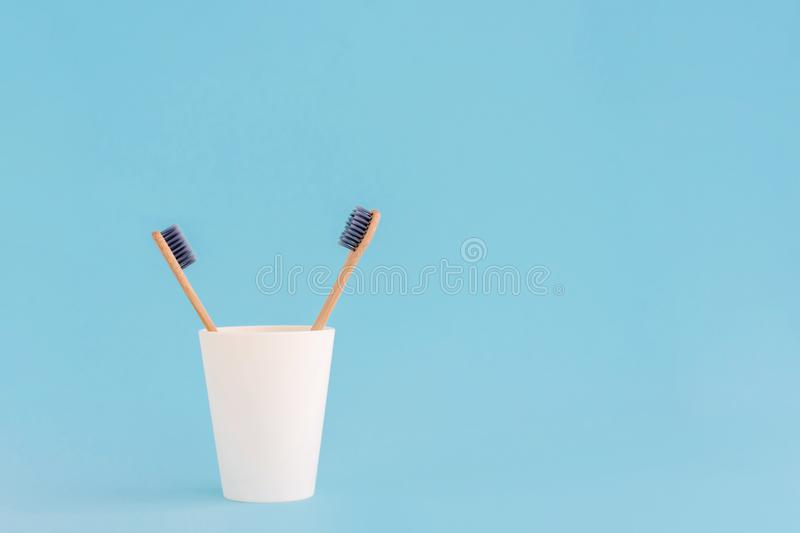 Two wooden toothbrushes in cup on blue background royalty free stock images