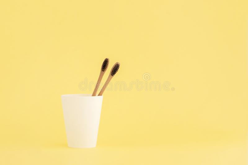 Two wooden toothbrushes in cup on yellow background royalty free stock images