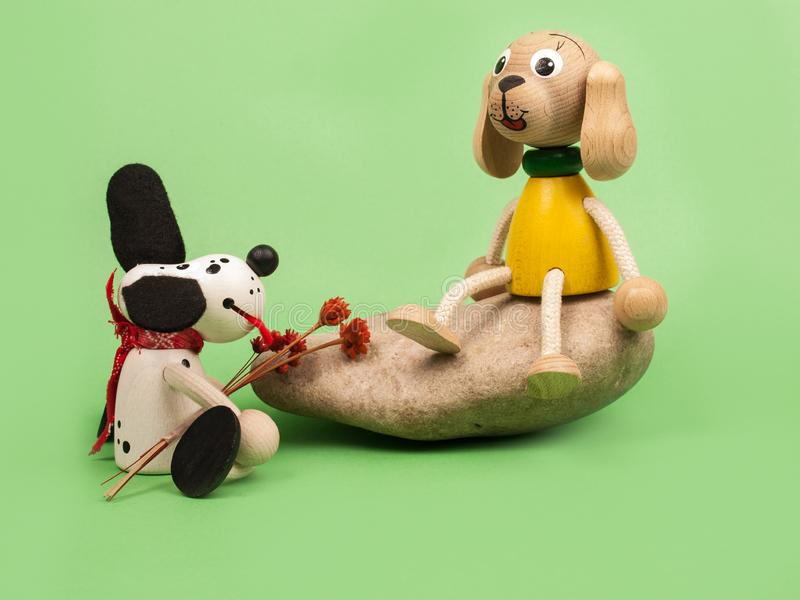 Wooden toy dogs on a green background. Two wooden toy dogs on a green background stock photo